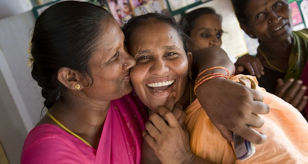 Two Indian ladies hugging and laughing, one is holding a mobile phone