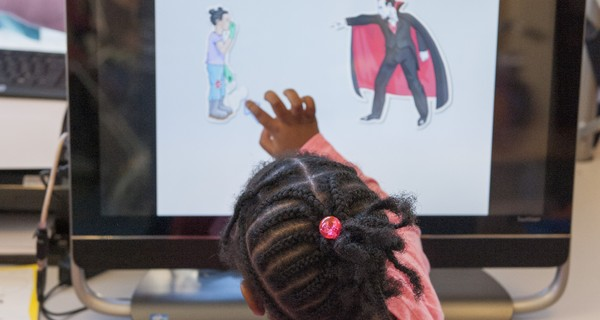 Child touching a cartoon character on a screen