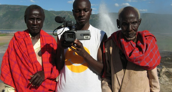 Three African men stood in a row, the middle man is holding a video camera