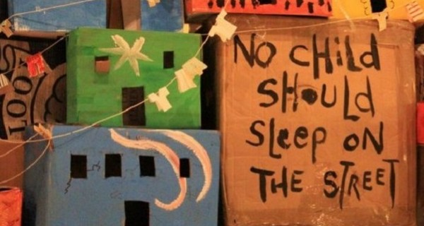 Boxes piled up - writing on one says 'No child should live on the street'