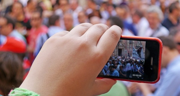 A close up of someone filming a protest on their mobile phone