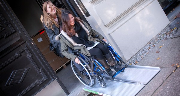 A wheelchair user coming out of a building down a ramp