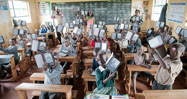 A classroom of African school children hold up their e-readers